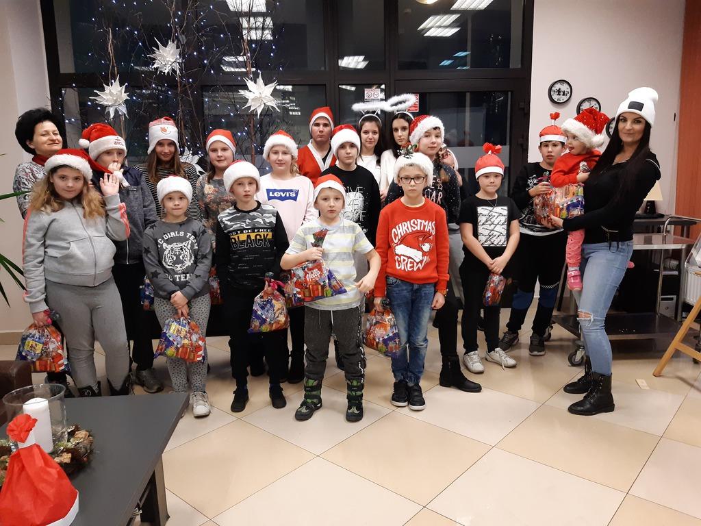 Grupa dzieci w czapkach mikołajowych z prezentami.
