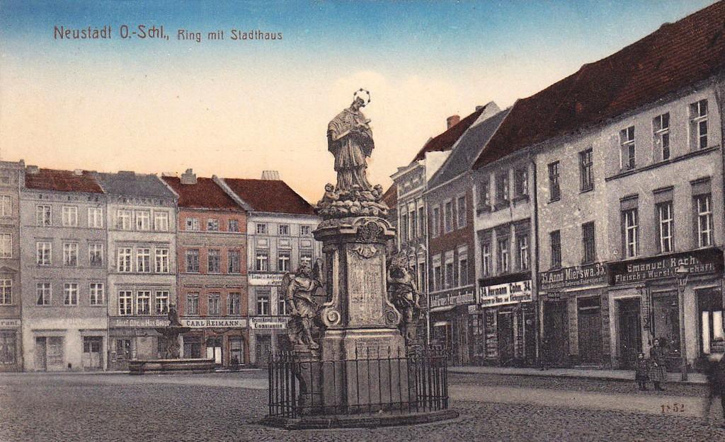 Stara pocztówka przedstawiająca rzeźbę Jana Nepomucena na rynku w Prudniku.Na drugim planie kamienice mieszczańskie