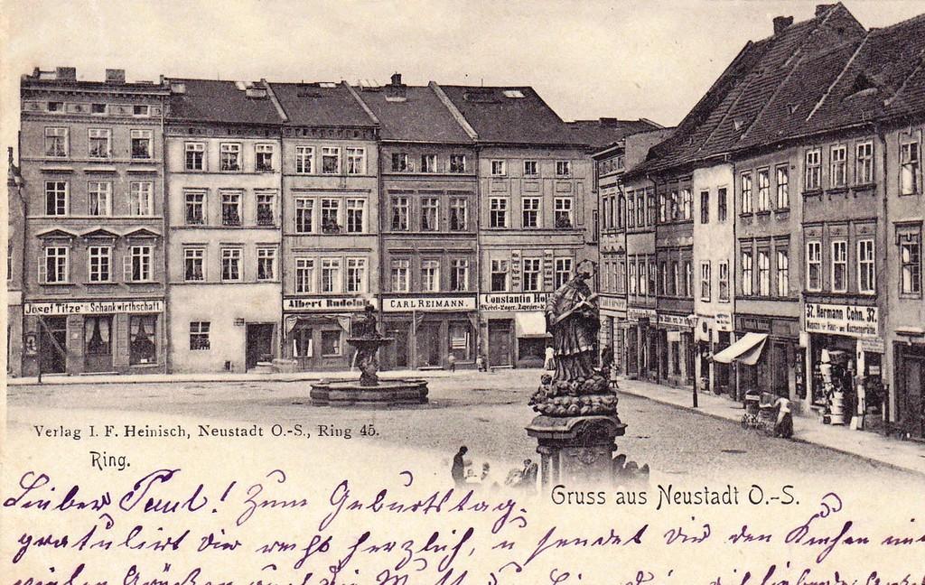 Stara pocztówka przedstawiająca rzeźbę Jana Nepomucena i fontannę na rynku w Prudniku. Na drugim planie kamienice mieszczańskie