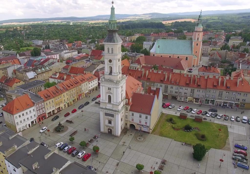 Zdjęcie panorama zabytkowego ratusza w Prudniku, wraz przyległymi kamienicami i kościołem parafialnym św Michała Archanioła. Na drugim planie panorama Gór Opawskich.