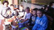Grupa dzieci przed schroniskiem wraz z opiekunem. Na stole figurki ceramiczne wykonane przez dzieci.
