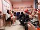 Grupa dzieci w czapkach mikołajkowych. Dzieci siedzą na krzesłach w sali. po przeciwnej stronie siedzą 3 osoby . Jedna przebrana za Mikołaja oraz dwie osoby przebrane za anioły.