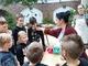 Warsztaty piernikarskie. Pani daje dzieciom do powąchania zawartość glinianego kubka.