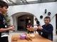 Dzieci stojące przy stołach w sali muzealnej. Na stołach lezą wałki do wałkowania ciasta oraz foremki.