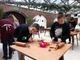 Zdjęcie przedstawiające grupę dzieci stojących przy stołach i lepiących ciastka z masy piernikowej w sali muzealnej.